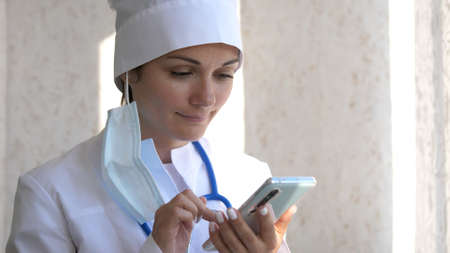 Doctor using mobile phone texting to patient informing about medical test results. Female doctor in white coat using modern smartphone device with touch screen.