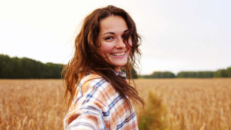 Brunette pretty woman in a field of ripe wheat turning smiling.