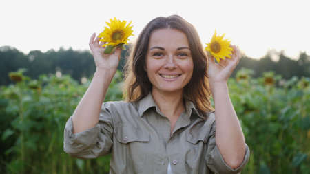 Young beautiful happy woman funny posing with sunflower flowers on a hot summer day