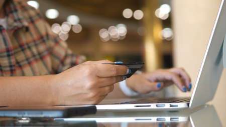 Female hands of cardholder holding credit card making e bank online payment. Woman consumer paying for purchase in web store using laptop technology. Ecommerce website payments concept.