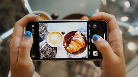 Close up of woman holds modern smartphone and taking pictures of her morning breakfast coffee and tasty croissant buns to share photos on social media resources