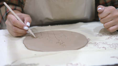Young woman draws patterns on a clay product. Pottery workshop. Stok Fotoğraf