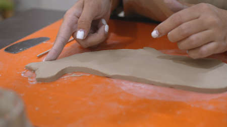 Young woman carving clay product edges Pottery workshop.