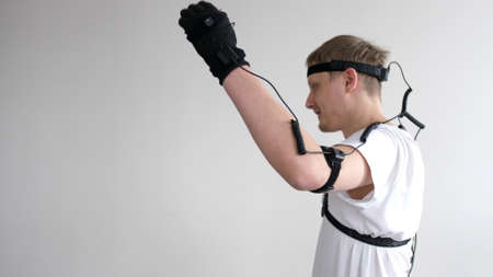athletic man with beard wears motion capture suit with sensors headset moving in virtual reality taking something and looking at his hands excited experience cyber space online