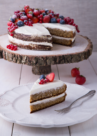 dessert fork: Piece of home made Earl Grey cake with cream cheese and berries and mashed strawberries in brandy inside, with strawberry, red currant and blueberry, on white plate with silver dessert fork