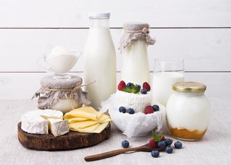 leche y derivados: Surtido de productos lácteos - leche, yogur, queso, camembert, queso hecho en casa con las bayas crema, crema agria, kéfir Foto de archivo