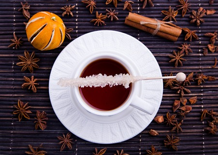 tea cosy: Winter cosy cup on the plate with knitted decor with rooibos tea and sugar stick atop, with dry mandarine, anise stars and cinnamon on black wood background