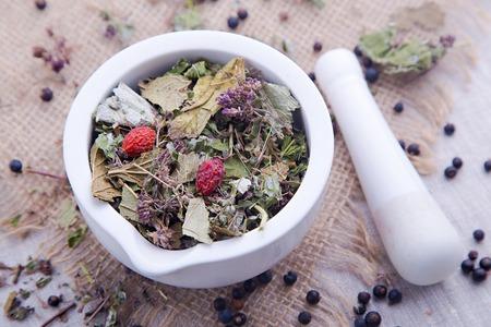 hojas secas: El té de hierbas con la zarzamora, hojas de menta secas y madera de brezo en el mortero blanco y con la maja