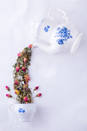 alice: Magic porcelain white with blue teapot pouring dry herbs and roses tea in the cup, Mad Hatter tea party Stock Photo
