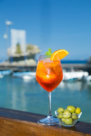 spritz: Cold glass of aperol spritz wit olive appetizer with sea and blue sky background