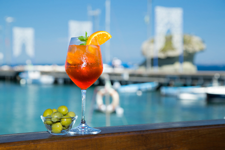 Cold glass of aperol spritz wit olives appetizer stand near the sea and boats