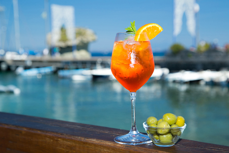spritz: Cold glass of aperol spritz wit olives appetizer stand near the sea and boats
