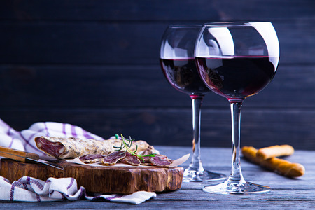 Glass of red wine with salami and grissini