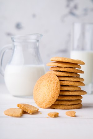 condensed: Tower from shortbread kamut cookies with glass and jug of milk