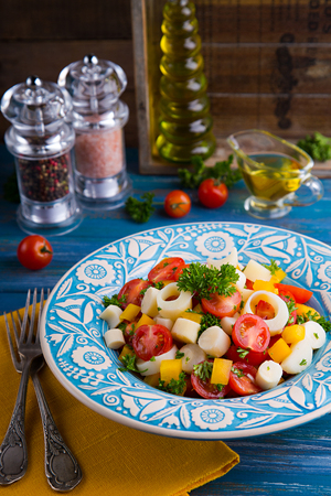 Fresh salad of heart of palm, cherry tomatoes, yellow bell pepper, garlic and parsley on wood background Stock Photo