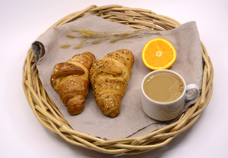 Croissants Cup of coffee and orange on a tray. Breakfast. Morning concept