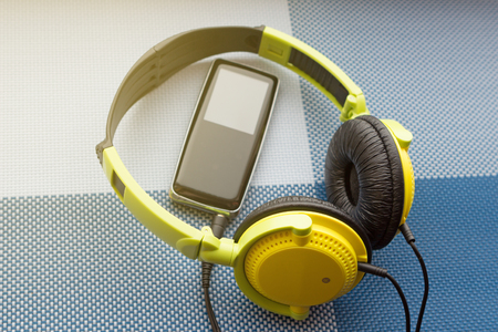 Headphones and player on a textured background Stock Photo