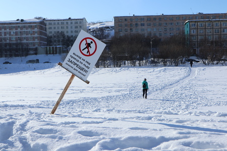 a man walks down the lake in the background prohibiting signs