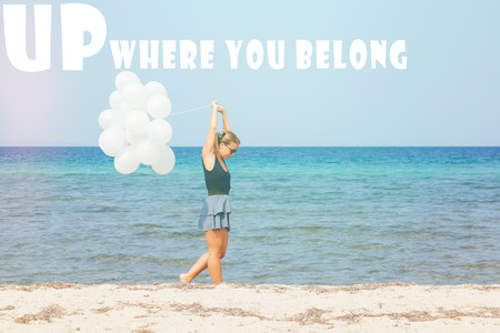 Young woman walking the beach with white ballons with written up where you belong