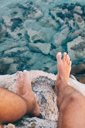 Young brave man sitting on a high cliff above the ocean ( POV view)