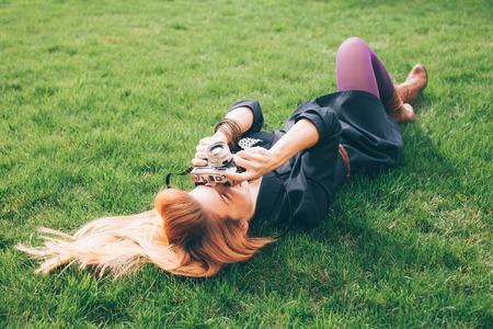 Giovani pantaloni a vita bassa fotografo femminile sdraiato sull'erba Archivio Fotografico - 64159228