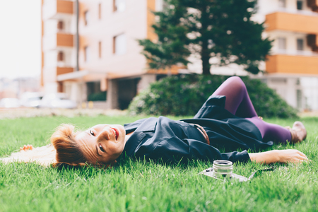 Young happy woman lying on the grass