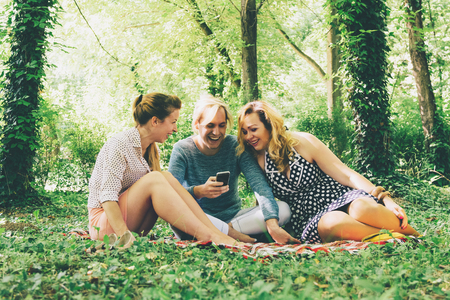 Group of young friends sitting on grass and relaxing Stock Photo