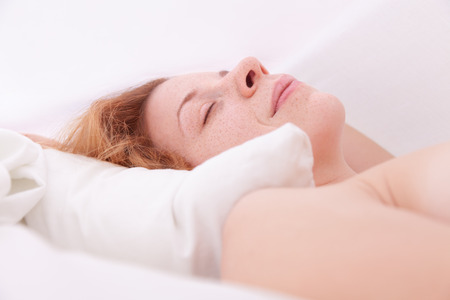 Young woman lying in the sheets Stock Photo