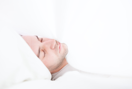 Young man lying in the sheets Stock Photo