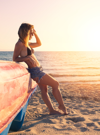 Young hipster woman watching the sunset on the beach 스톡 콘텐츠