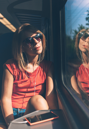 Young woman listening to the music on the train
