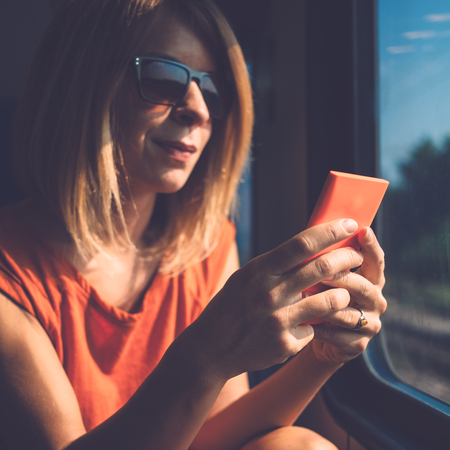 Young woman using smartphone in public transport