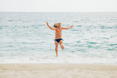 Young woman running into the sea 스톡 콘텐츠