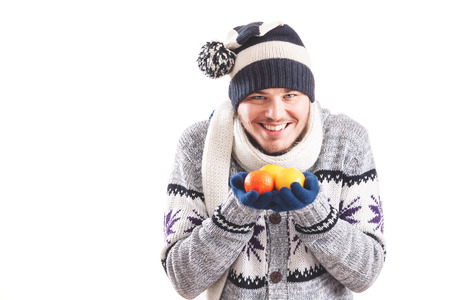 Young man dressed warm holding lemons and oranges 스톡 콘텐츠