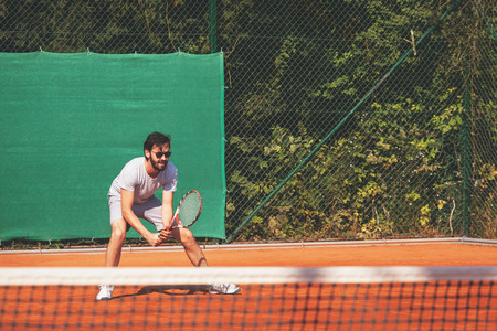 Young man playing tennis on the open court