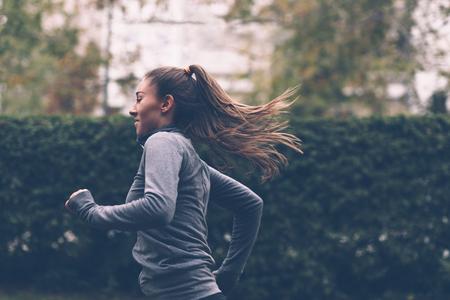 Woman running. Female runner jogging, training for marathon. Fit girl fitness athlete model exercising outdoor. 스톡 콘텐츠