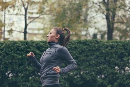 fall winter: Woman running. Female runner jogging, training for marathon. Fit girl fitness athlete model exercising outdoor. Stock Photo