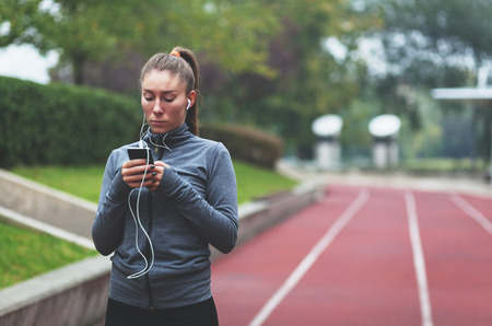 Young sporty woman listening to music using a smartphone
