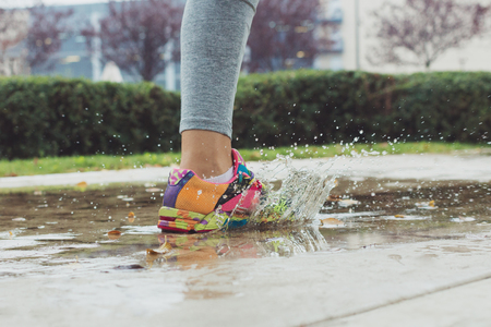 Young woman running on asphalt sports field in rainy weather splashing puddles.