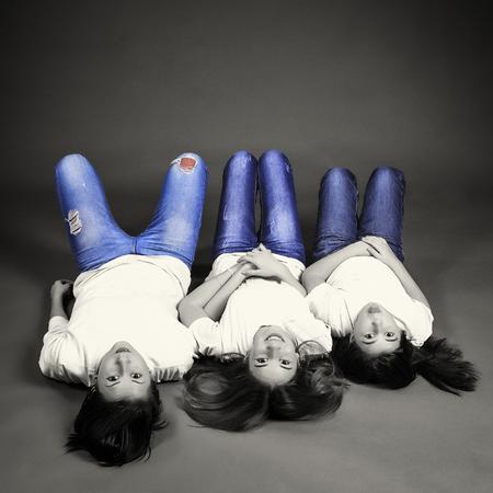 cabeza abajo: Tres hermanas que mienten en el suelo boca abajo