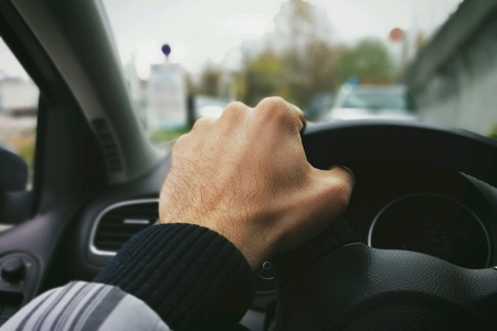 Hand on the wheel driving a car