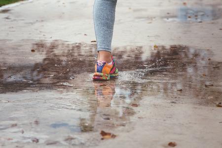 비오는 날씨 튀는 웅덩이에 아스팔트 스포츠 분야에서 실행중인 젊은 여자.