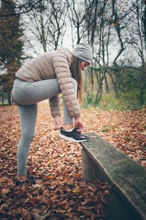 Young woman getting ready for jogging in the park Stock Photo