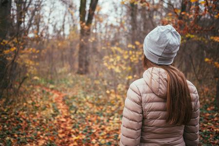 가을 숲에 직면 젊은 여자
