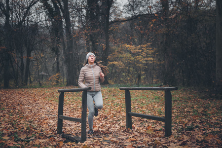 Young woman jogging on a cold day in the park