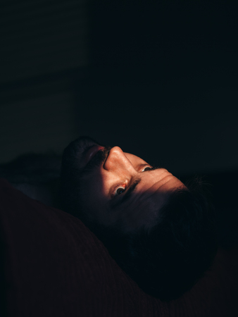 Young man sad and depressed in the dark Stock Photo