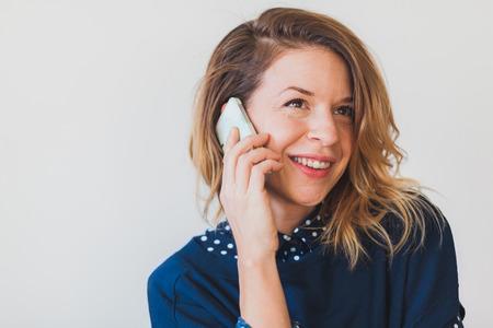 흰색 배경에 전화로 얘기 젊은 여자 스톡 콘텐츠