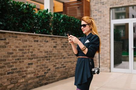 그녀의 건물의 앞에 그녀의 스마트 폰을 사용하는 젊은 여자