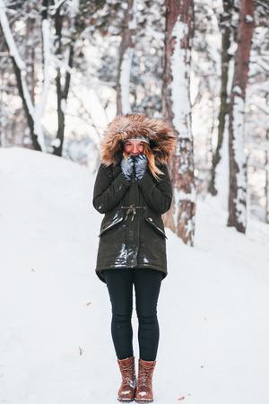 Cute giovane donna in piedi nella neve nel parco