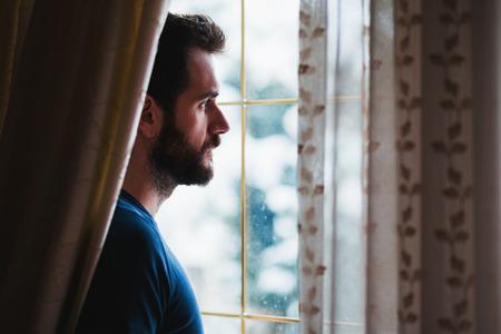 Giovane pazzo in piedi triste alla finestra guardando fuori